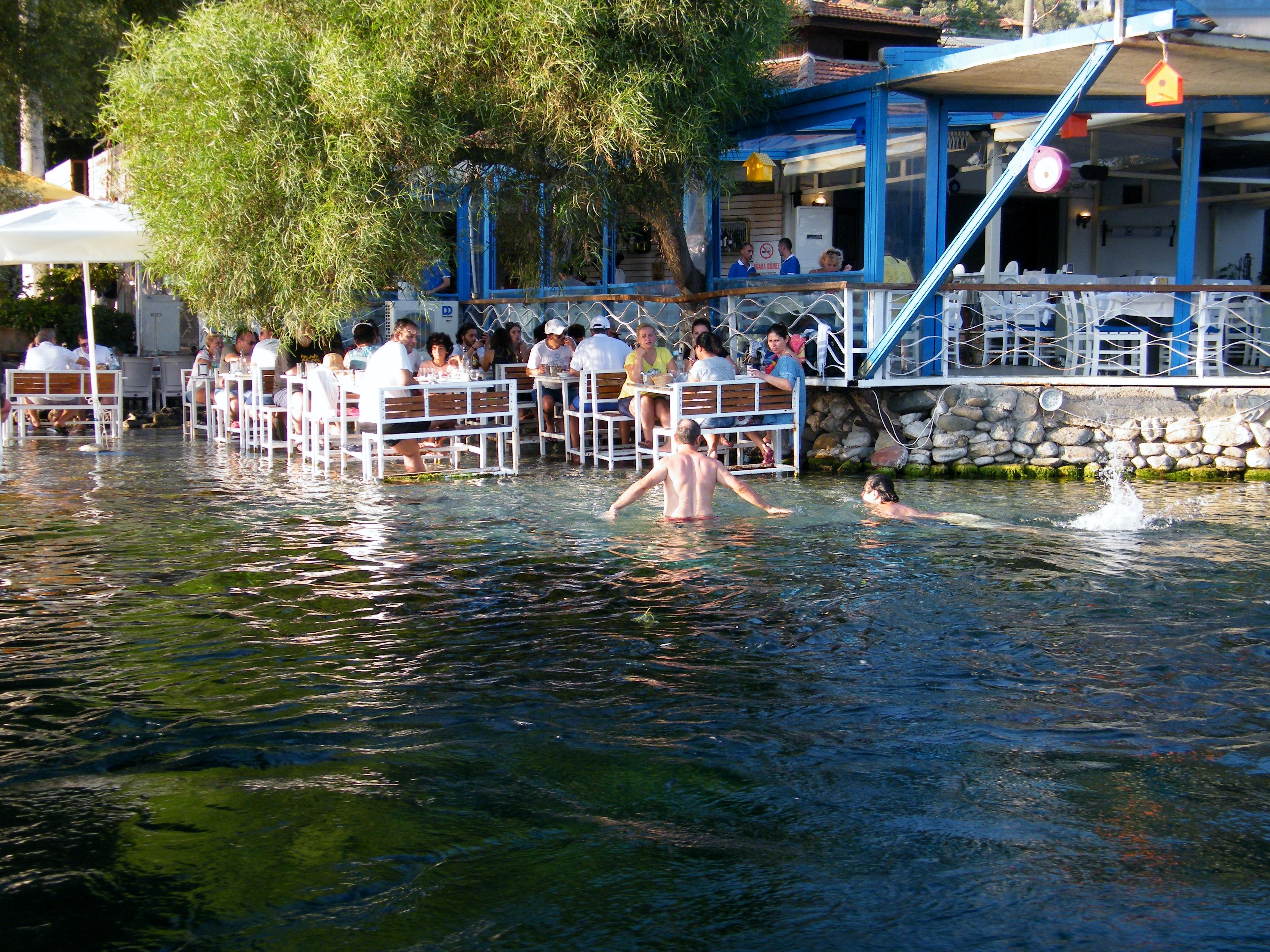 Gente que se baña entre las mesas de un restaurantes posadas en la orilla del río de Akyaka en el Egeo turco / J.M Akyaka en el Egeo turco